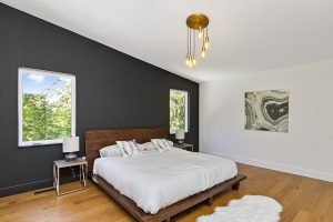 The master bedroom is expansive, boasting vaulted ceilings and a daring, yet stunning black feature wall